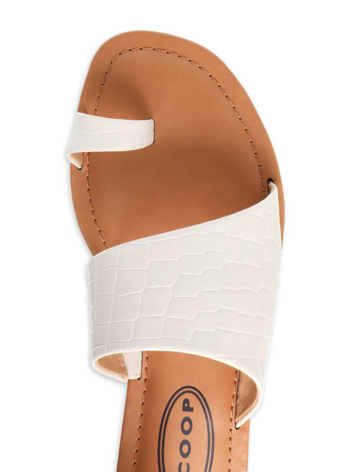 A top-down view of a white toe-ring sandal with a tan leather insole