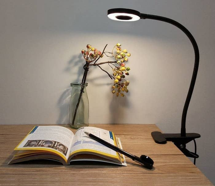 A lamp is angled over a book on a table