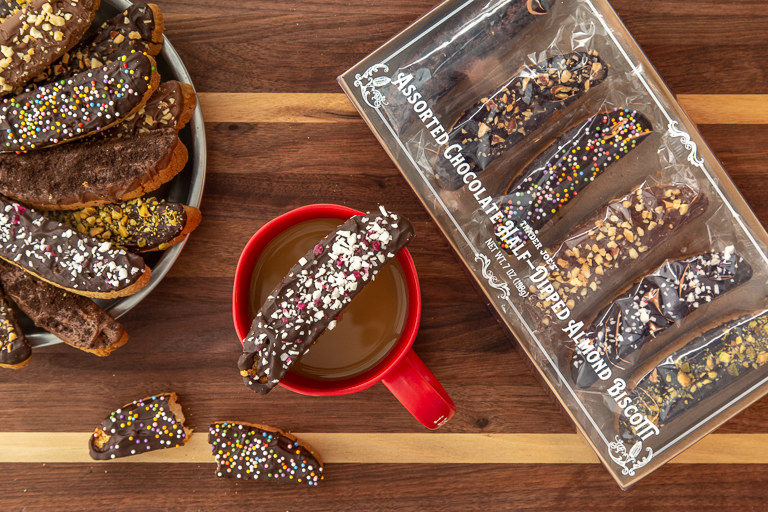 A cup of coffee sits upon a wooden table. On top of the cup balances a chocolate biscotti with candy cane pieces baked in. The coffee cup is surrounded by biscotti cookies.