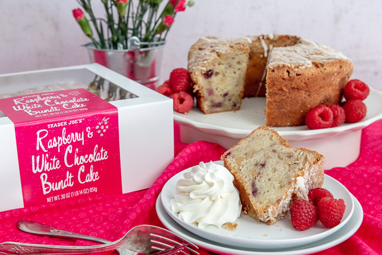 """A box that reads, """"Raspberry white chocolate bundt cake"""" sits on a tablecloth next to two plates. One large plate contains the bundt cake surrounded by raspberries, and one slice is taken out. The cut slice sits on another plate, next to whipped cream"""