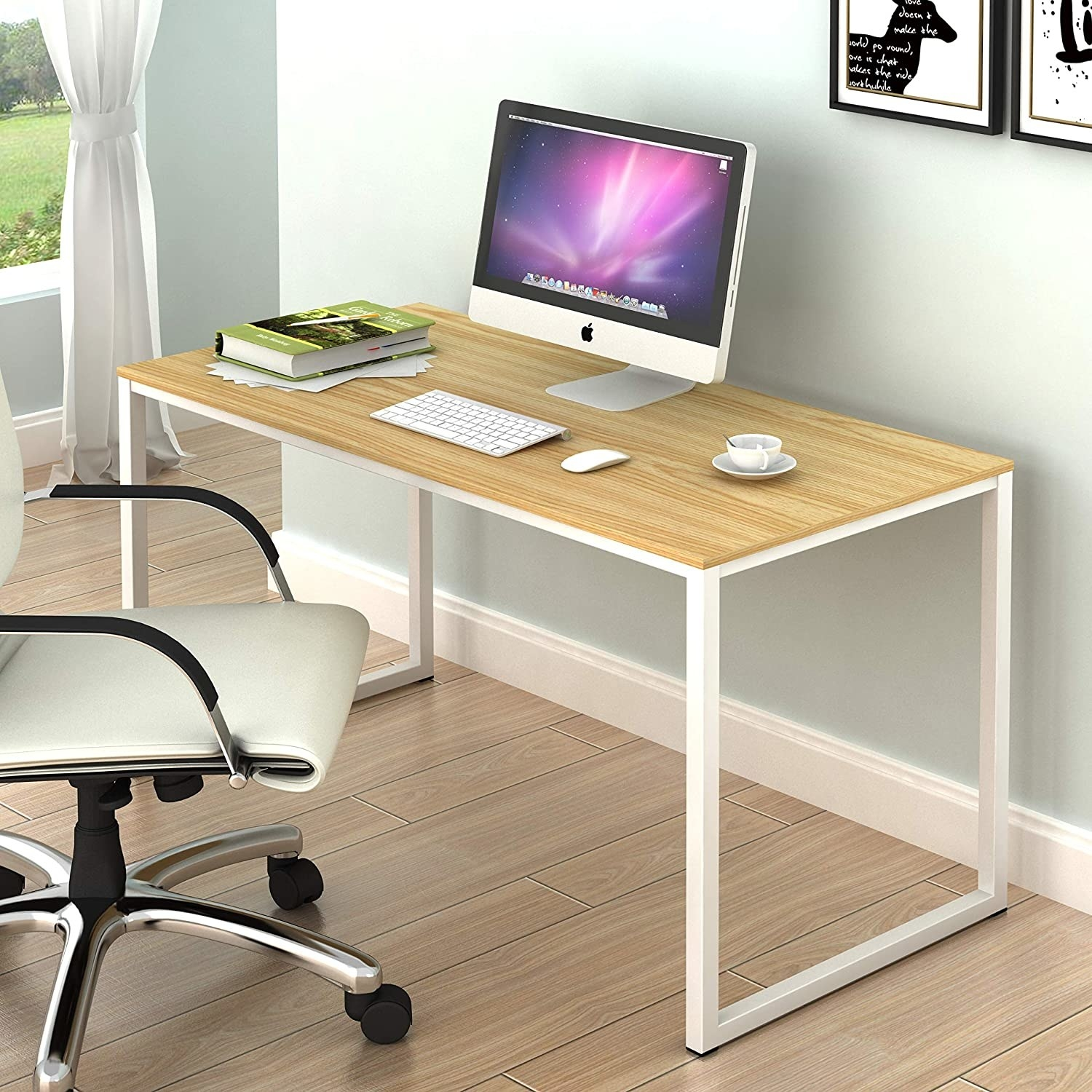 A desk in an office with a chair and a monitor