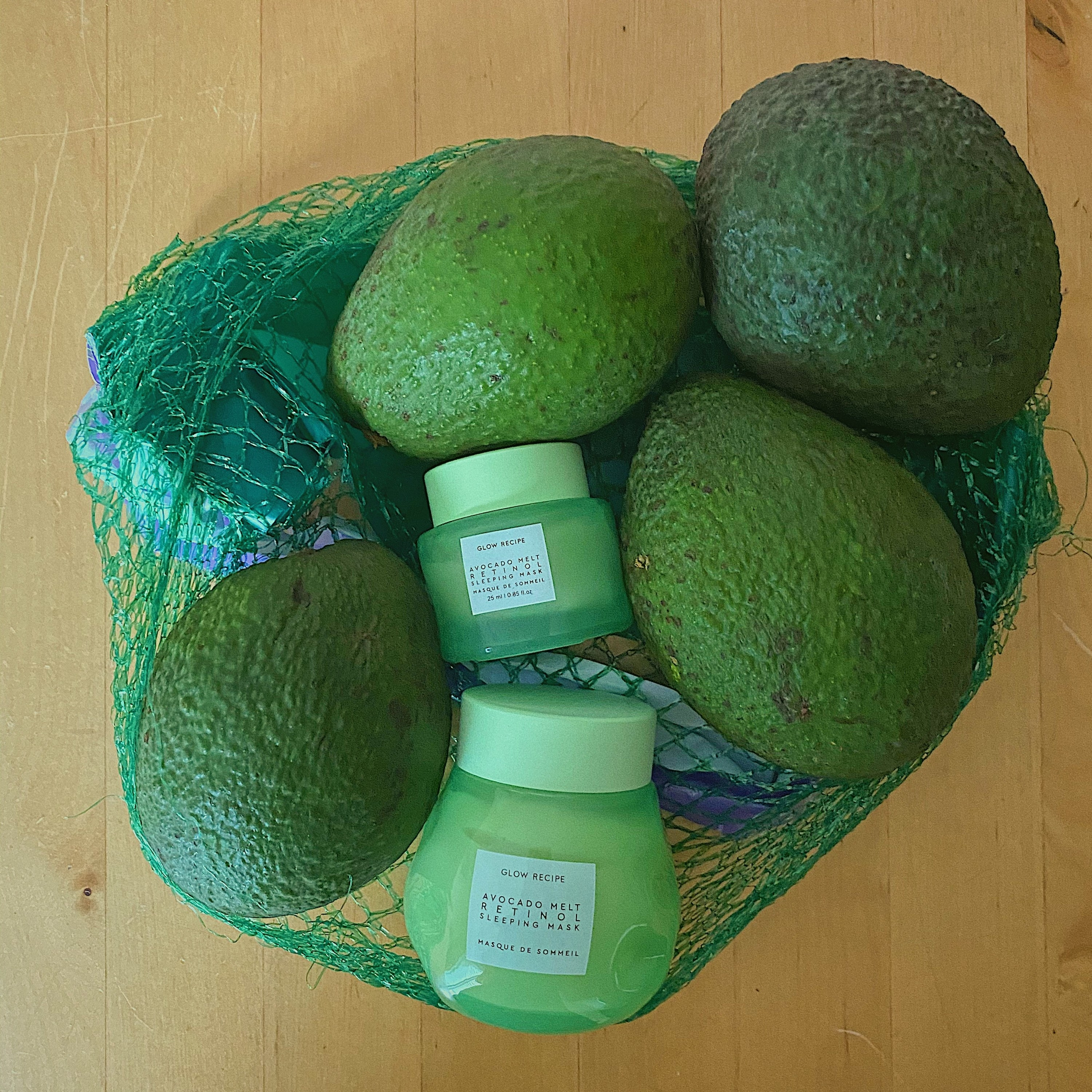 the avocado sleeping mask in a glass green jar in a pile of avocados