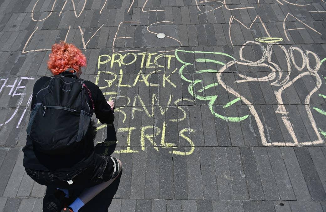 "A woman writes ""Protect Black Trans Girls"" in chalk on a sidewalk"