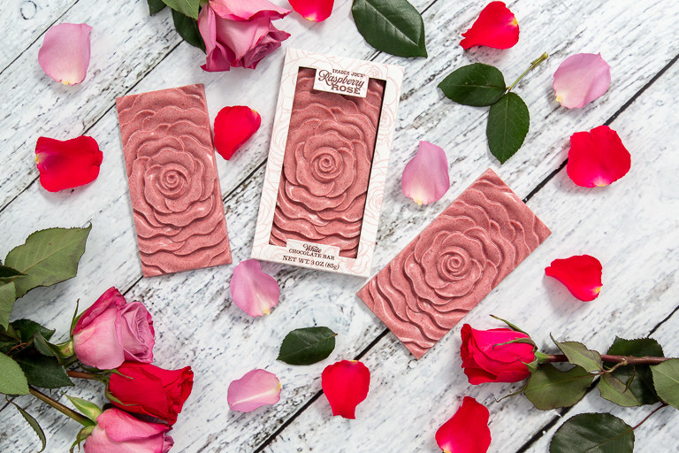 Rectangular chocolate bars with rose designs sit upon a wooden table. Surrounding the chocolate bars are rose petals.