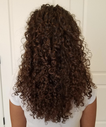 Reviewer with sleek curly hair after using the conditioning set
