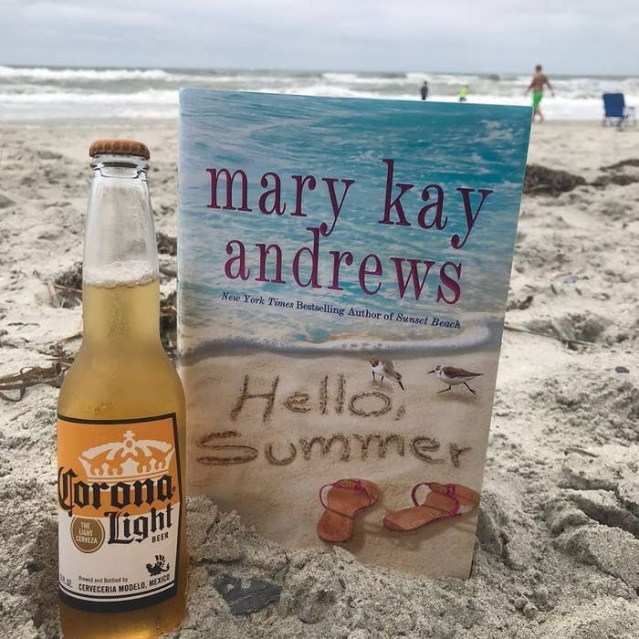 The book propped up in the sand with a beer