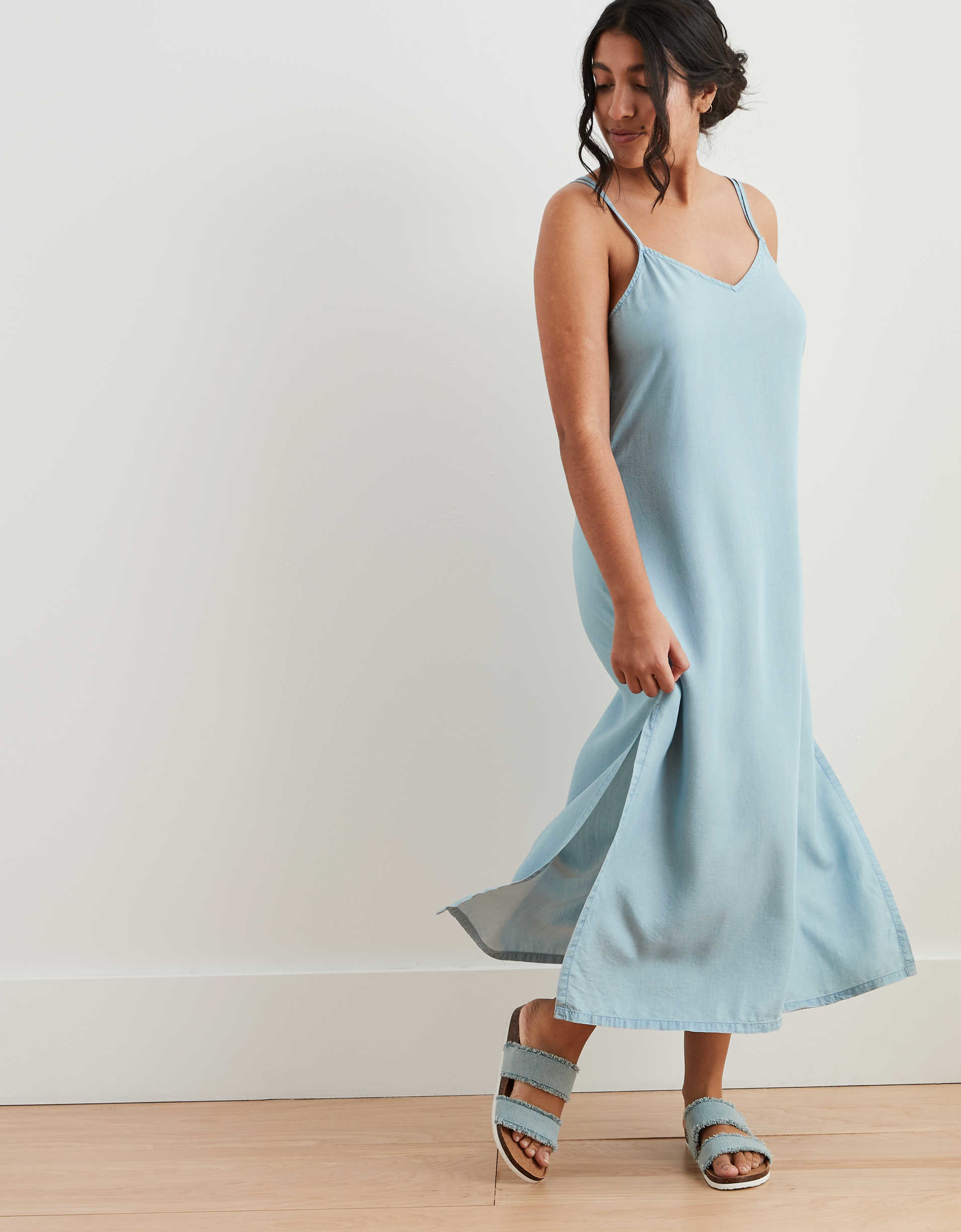 model wearing a spaghetti strap slip dress in light blue chambray fabric with side slits just past the knee