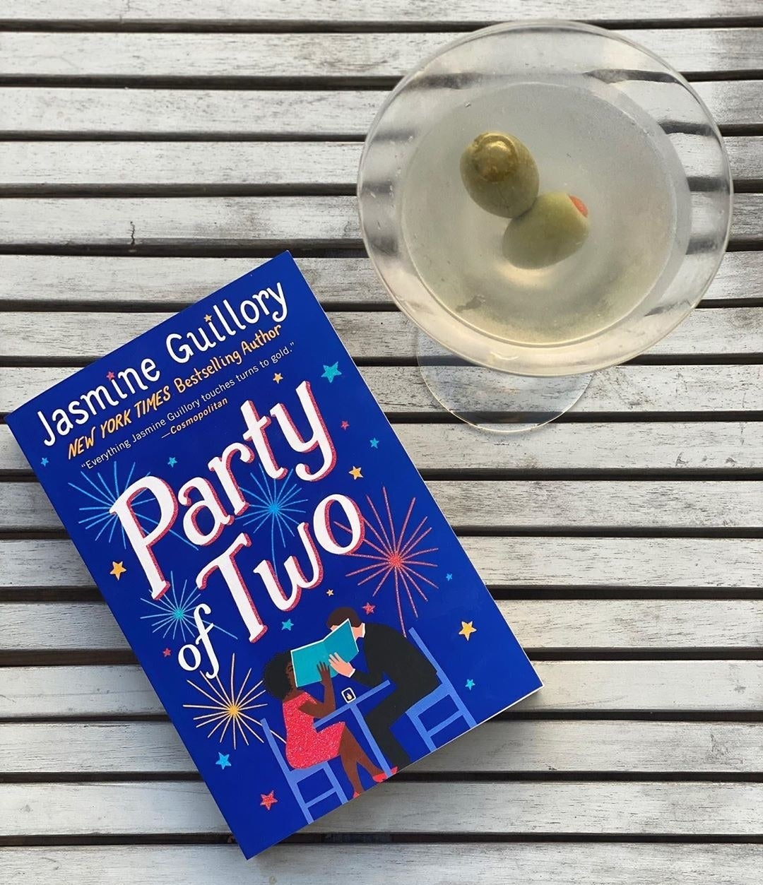 The book is flat on a table with a martini