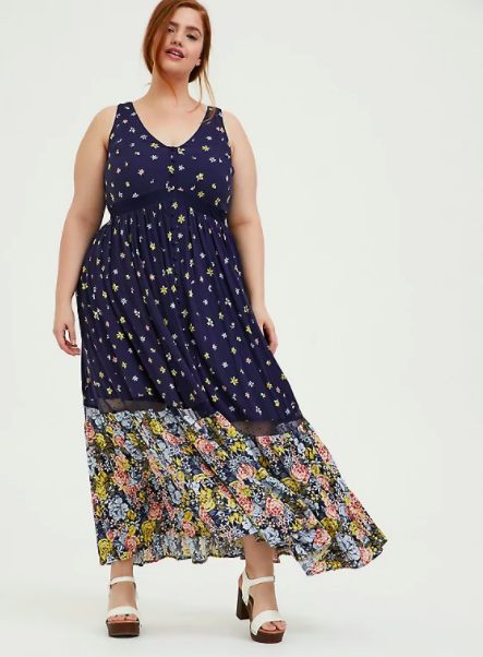 model wearing the sleeveless maxi dress with navy floral print then multicolor floral print at bottom starting at knees