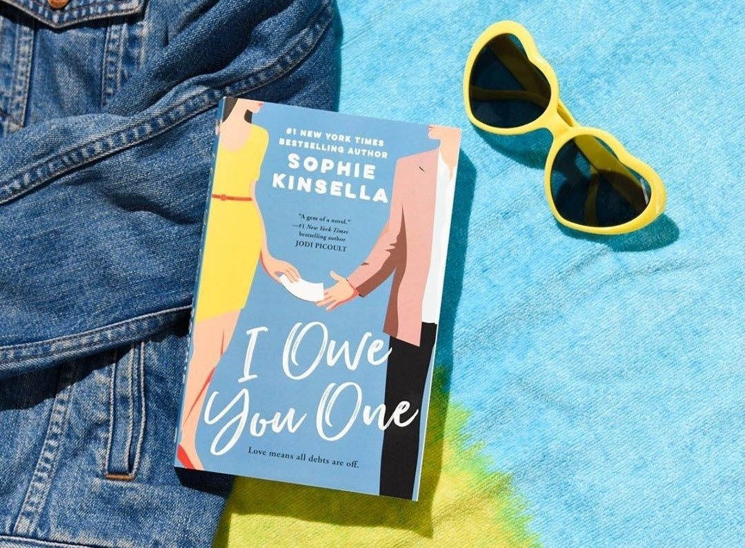 The book against a towel with a denim jacket and heartshaped sunglasses