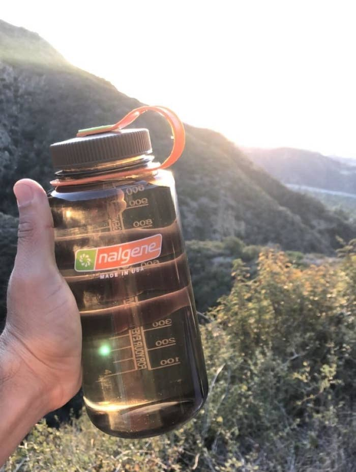 Reviewer holding their water bottle while hiking
