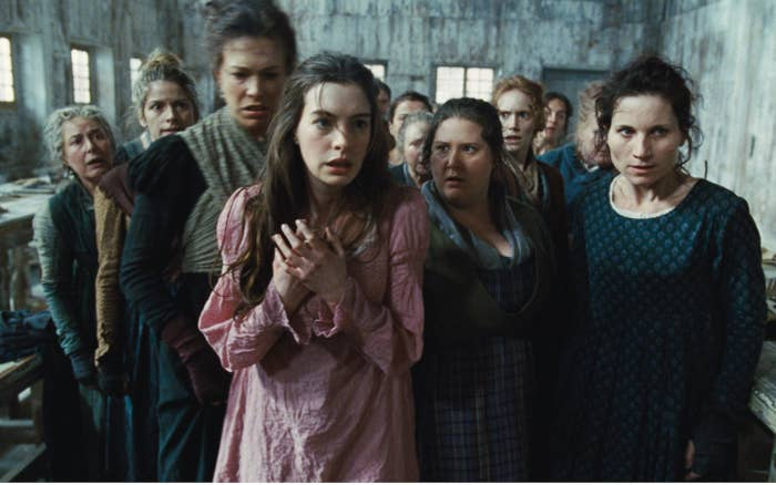 Anne Hathaway looks scared among a group of women in Les Misérables