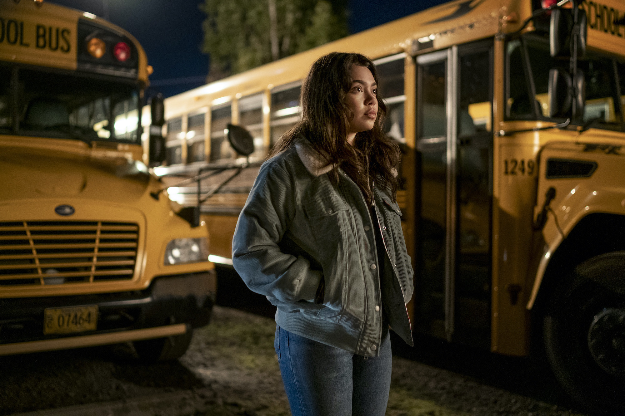 Auli'i Cravalho stands in front of two school buses at night in All Together Now