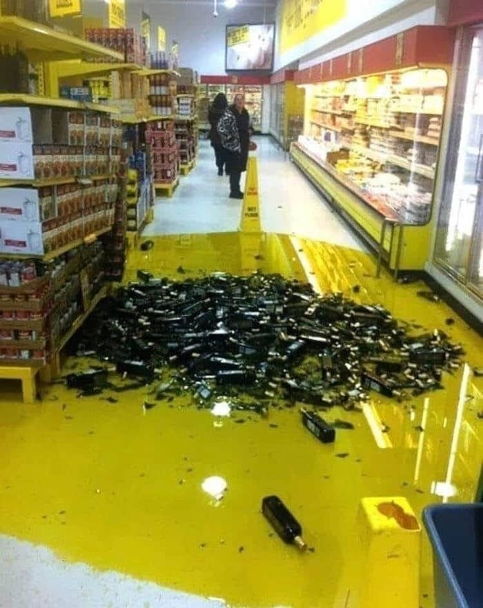 A grocery aisle with dozens of broken bottles of olive oil.