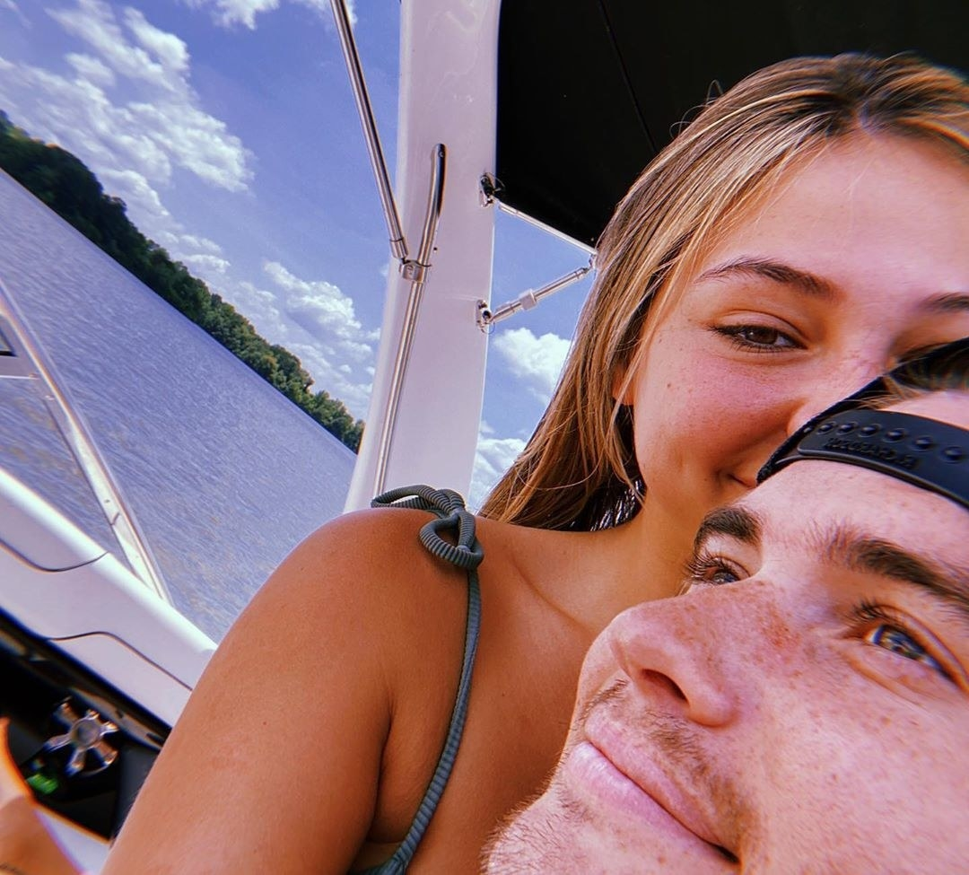 A close up of Chase Stokes and Madelyn Cline cuddling on a boat.