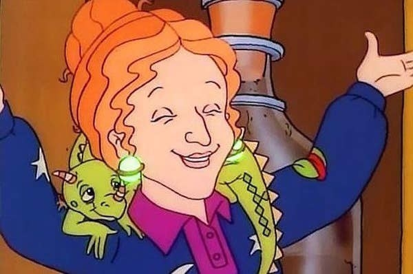 Screenshot of the cartoon Miss Frizzle smiling with her hands up, with her pet lizard, Liz, around her shoulders.
