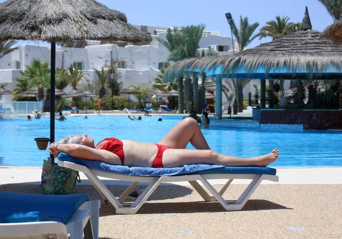 A woman in a bikini lounges on a deck chair under a thatch umbrella next to a hotel pool where people are swimming