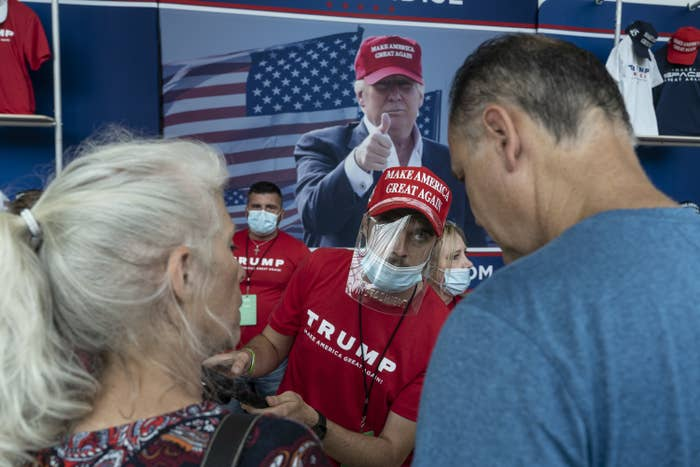 """A vendor at a rally wears a """"Make America Great Again"""" hat and T-shirt, protective face shield, and face mask"""