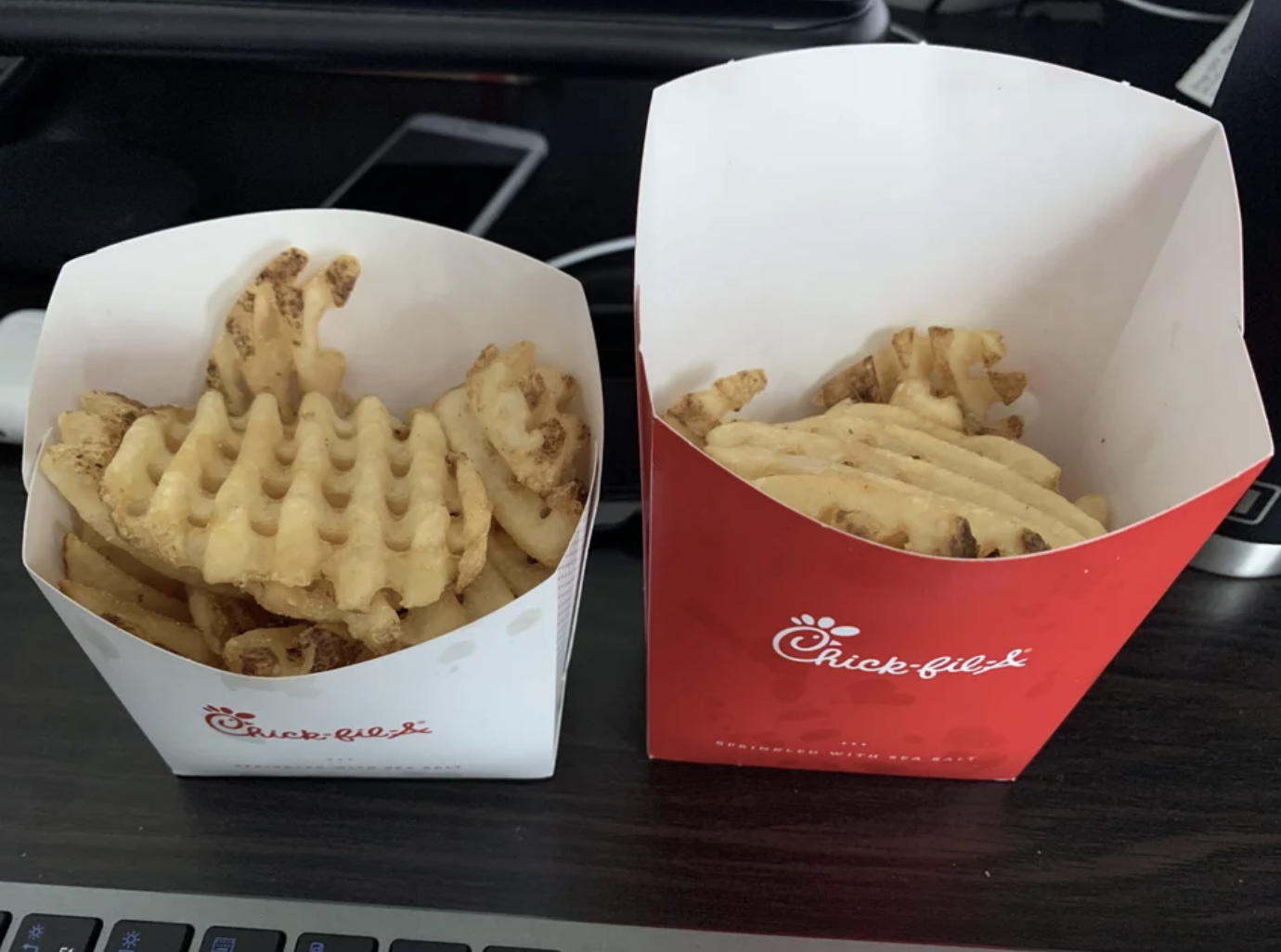 A small fry with more fries in it than the large fry next to it. They're from Chick-fil-A