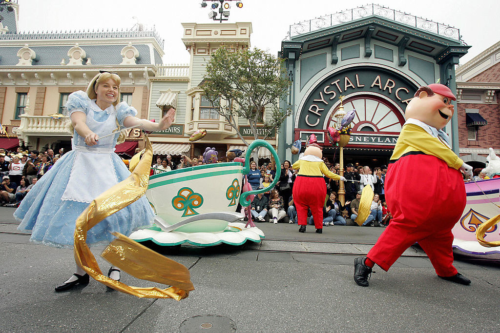 Characters from Alice in Wonderland dance down Disneyland Main Street.