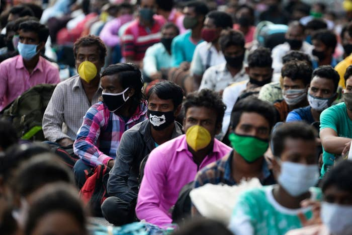 Men wearing face masks sit on the ground in rows