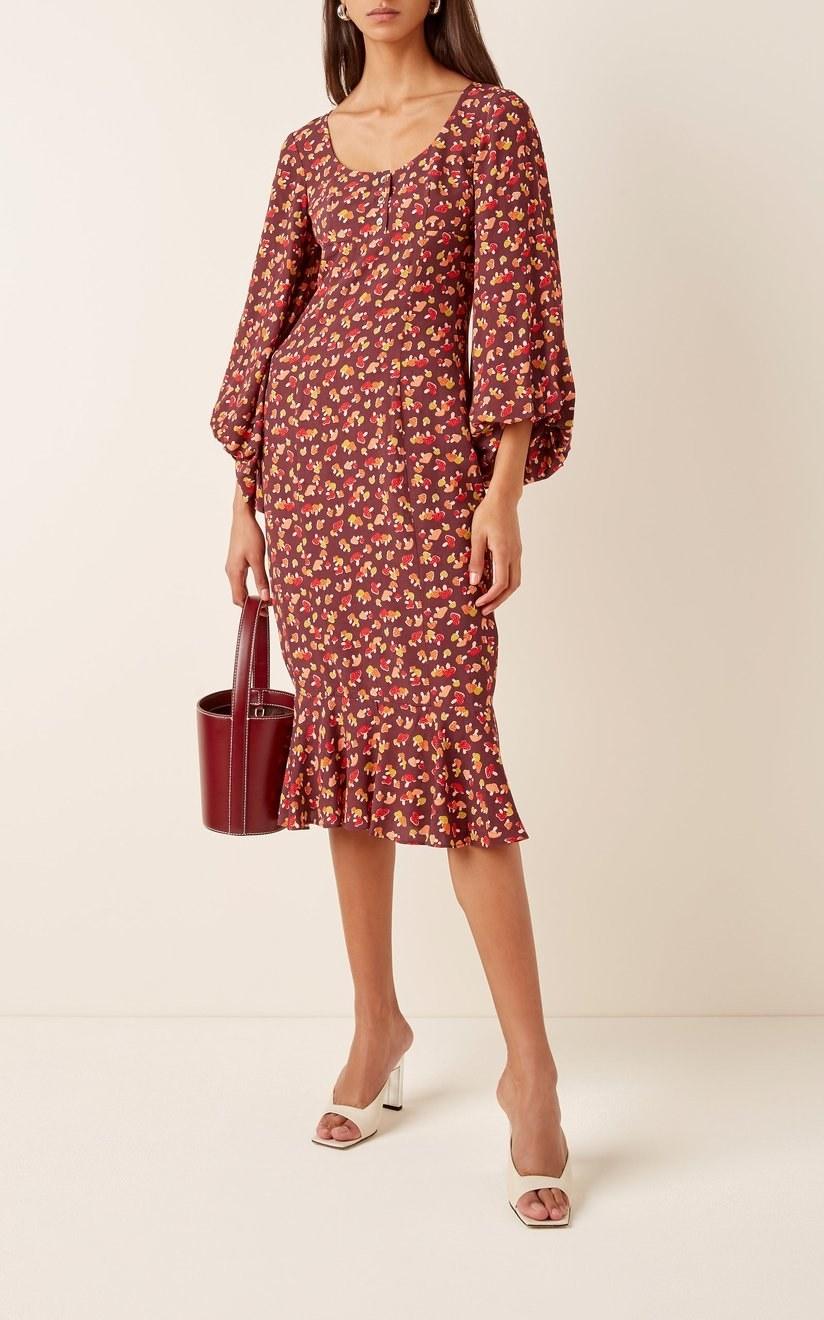 A model wearing Staud's Lara floral-print crepe dress.