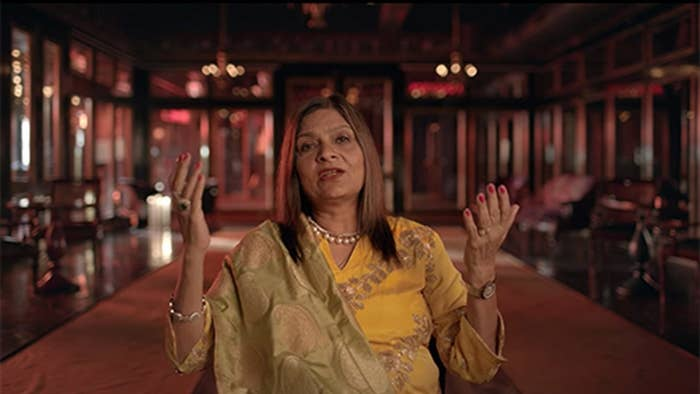 "Sima Taparia from ""Indian Matchmaking"" in a talking head confessional while wearing a yellow sari."