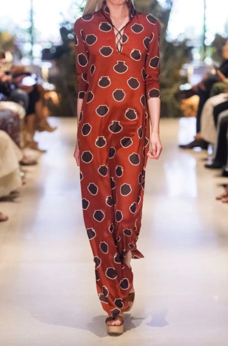A model wearing the Johanna Ortiz lace-up printed silk crepe de chine maxi dress down the runway.