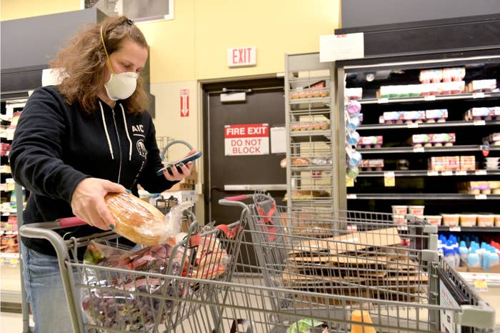 A woman in a grocery store checks the Instacart app on her phone as she shops