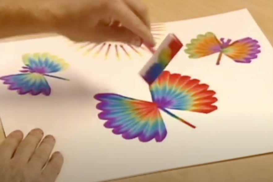 A screenshot of a kid painting rainbow butterflies with Rainbow Art.