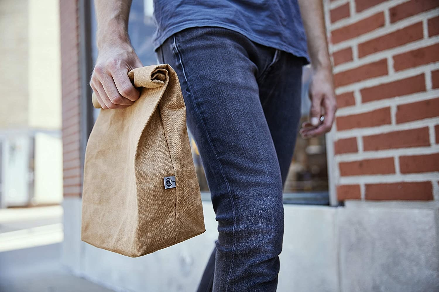 A model carrying a brown canvas lunch bag