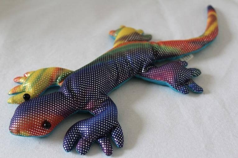 A photo of a stuffed lizard made with a rainbow-colored iridescent fabric.