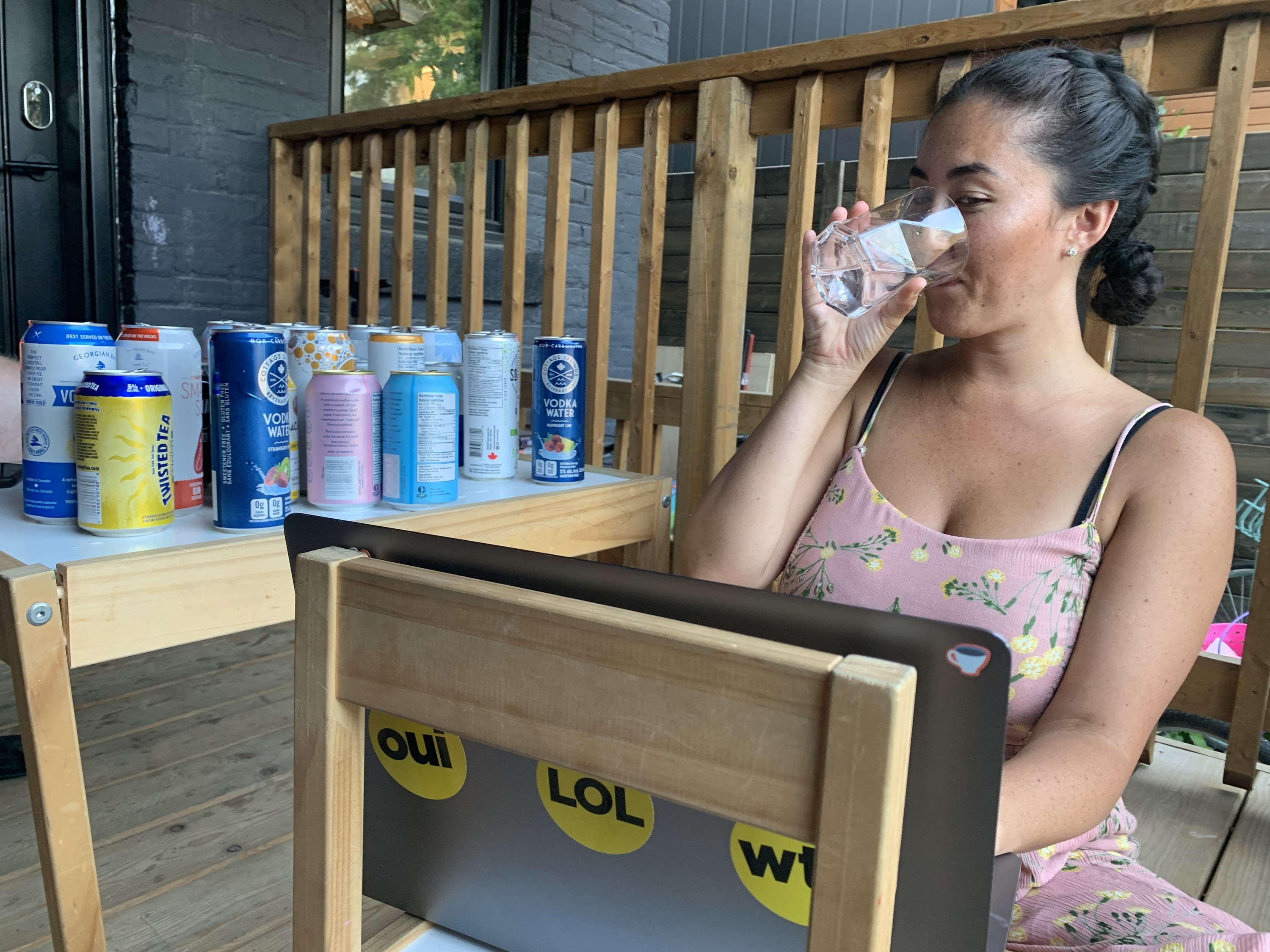 A photo of Liza sitting on a deck in front of her computer sipping a drink while cans of other drinks rest beside her on a table.