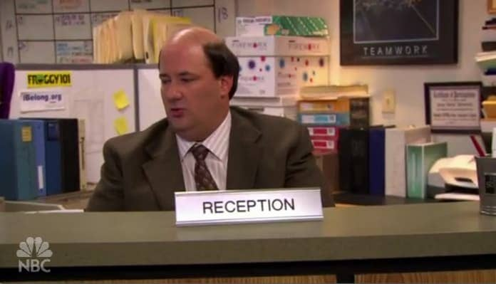 Kevin sitting at a reception desk in 'The Office'