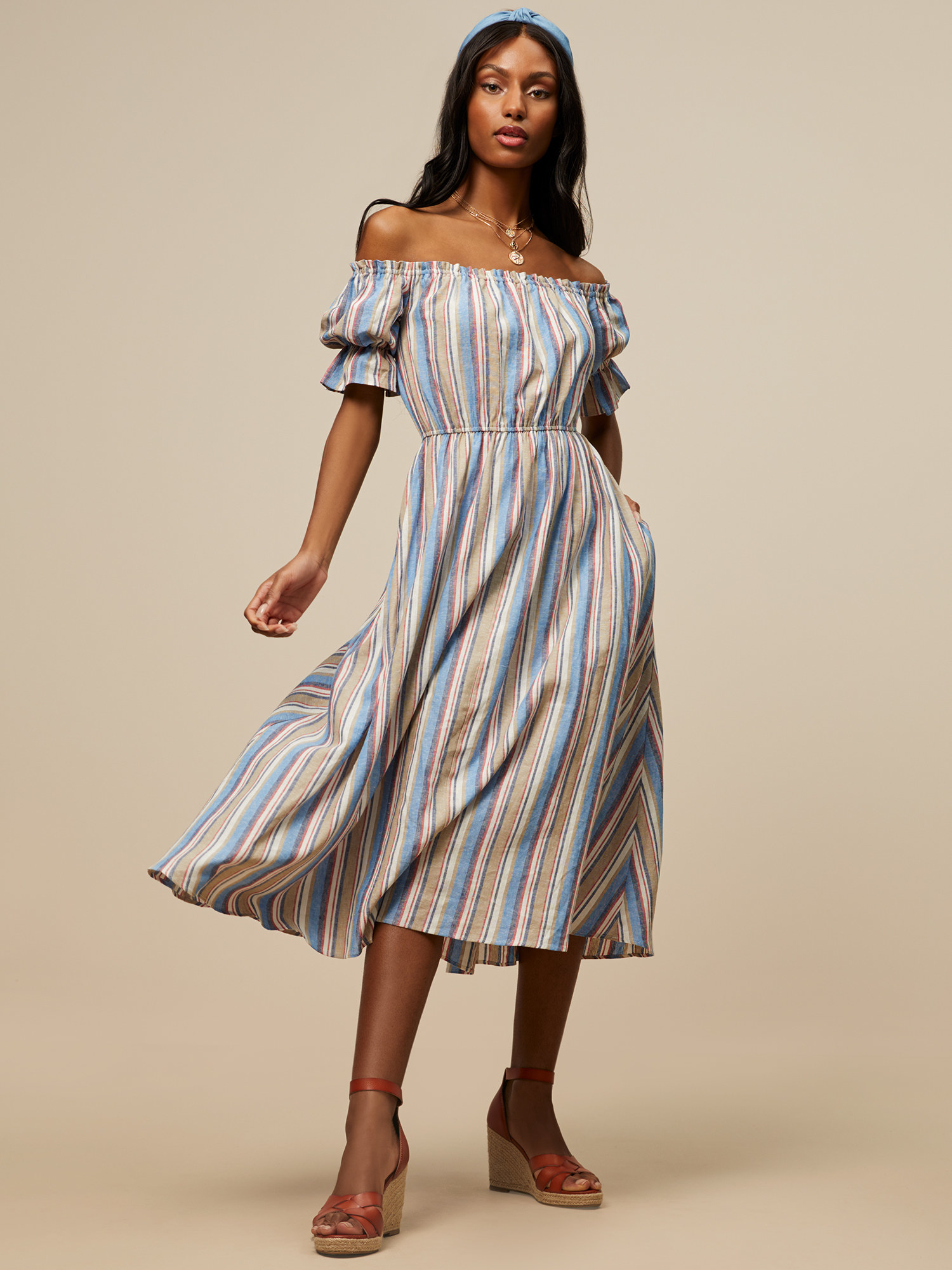a model in a dress with blue pink and tan vertical stripes