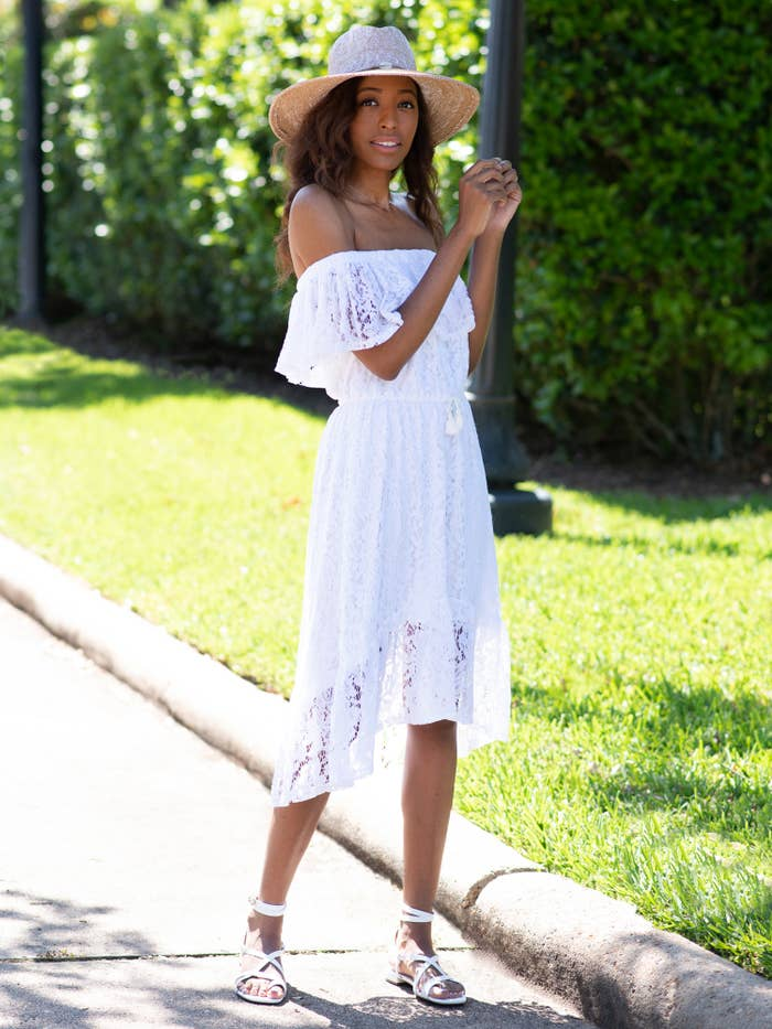 a model in a white off the shoulder lace dress