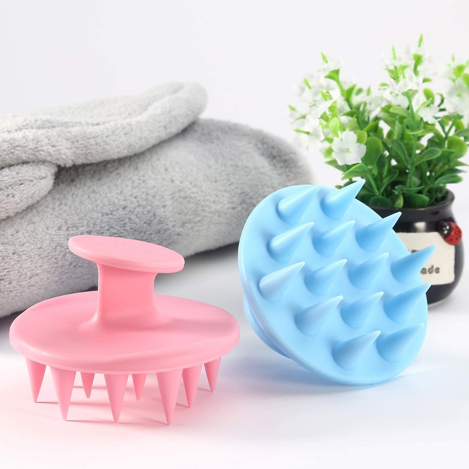 Two scalp massagers next to a towel and a plant