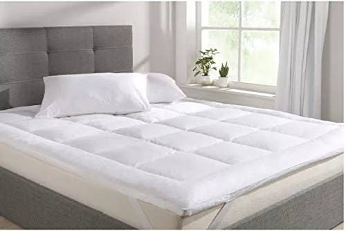 A white mattress topper on a double bed