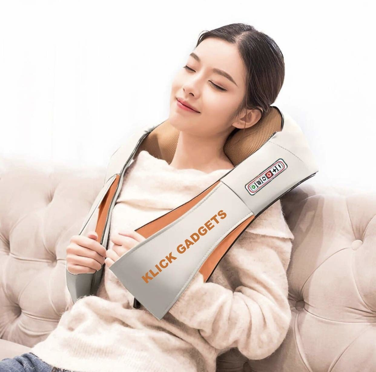 A woman using a neck and shoulder massager on a couch