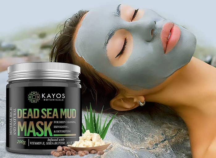 A woman with a mud mask on lying next to a container of Kayos Dead Sea Mud Mask