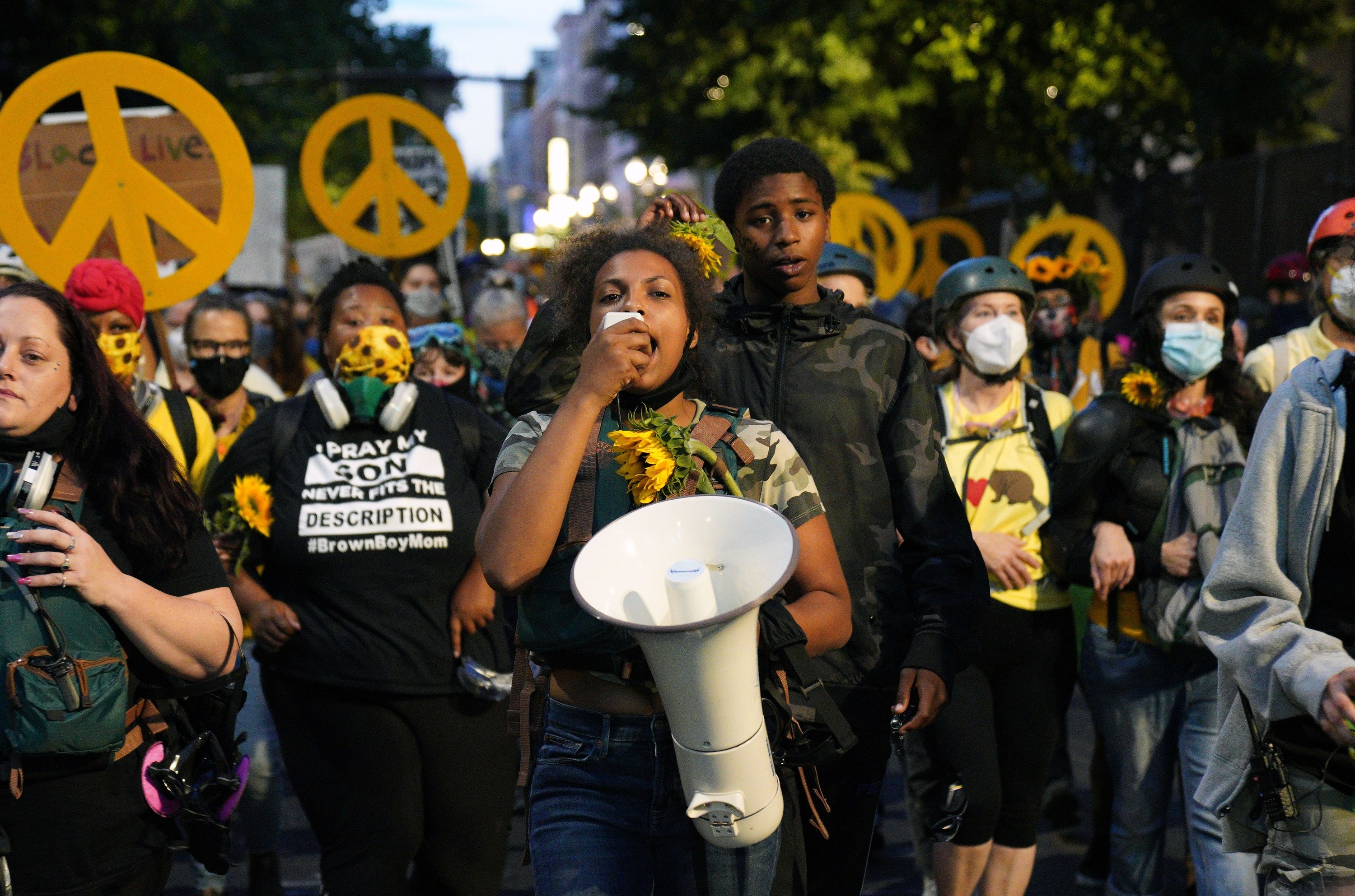 A young Black woman protester speaks into a megaphone in front of a group of demonstrators carrying peace signs