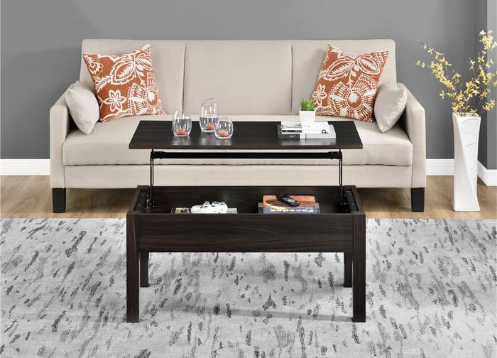 A black wood coffee table with the top lifted off