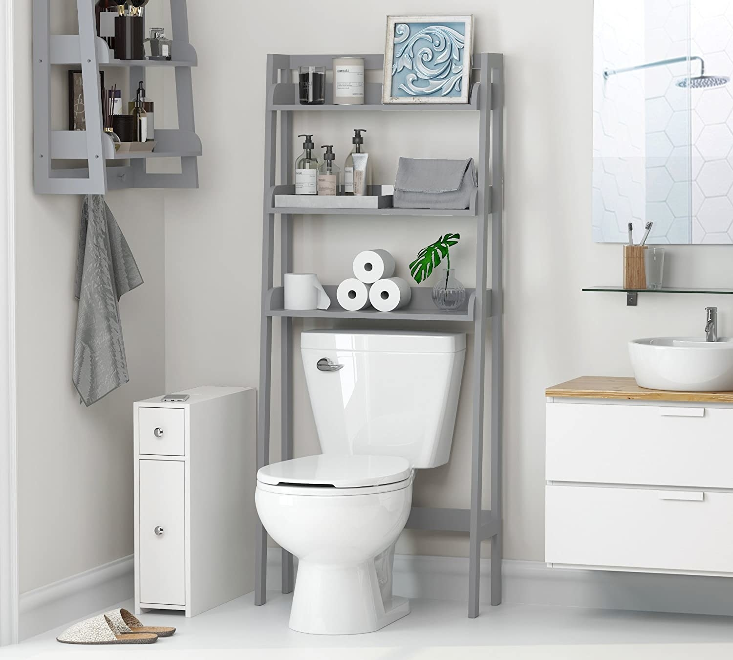 The shelf perched over a toilet and neatly stacked with bathroom supplies