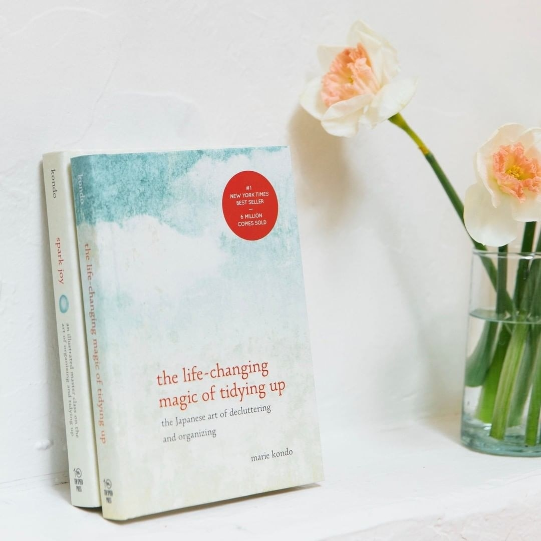 A copy of Marie Kondo's book The Life-Changing Magic of Tidying Up leaning against a wall
