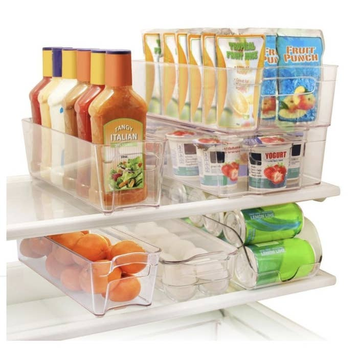 Food stacked in six plastic clear organizers in a fridge