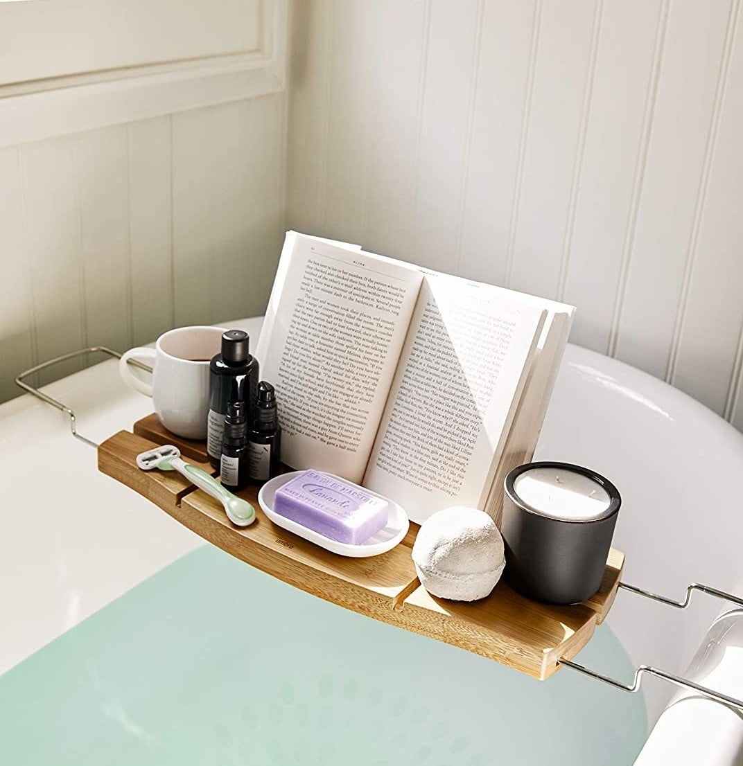 The bath tub caddy perched over a tub and topped with a book a candle a razor a bath bomb and other beauty products