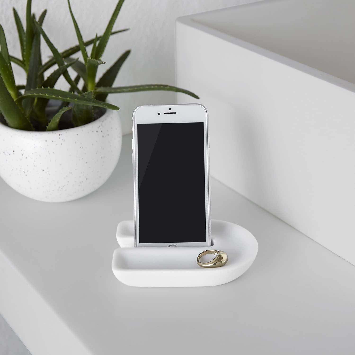 The phone holder on a counter with a phone and a gold ring on it