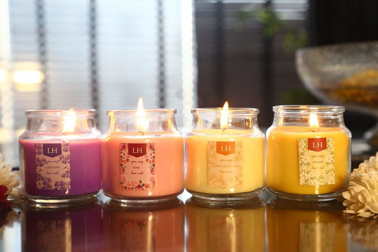 Four jars of lit aromatherapy candles of different scents on a table