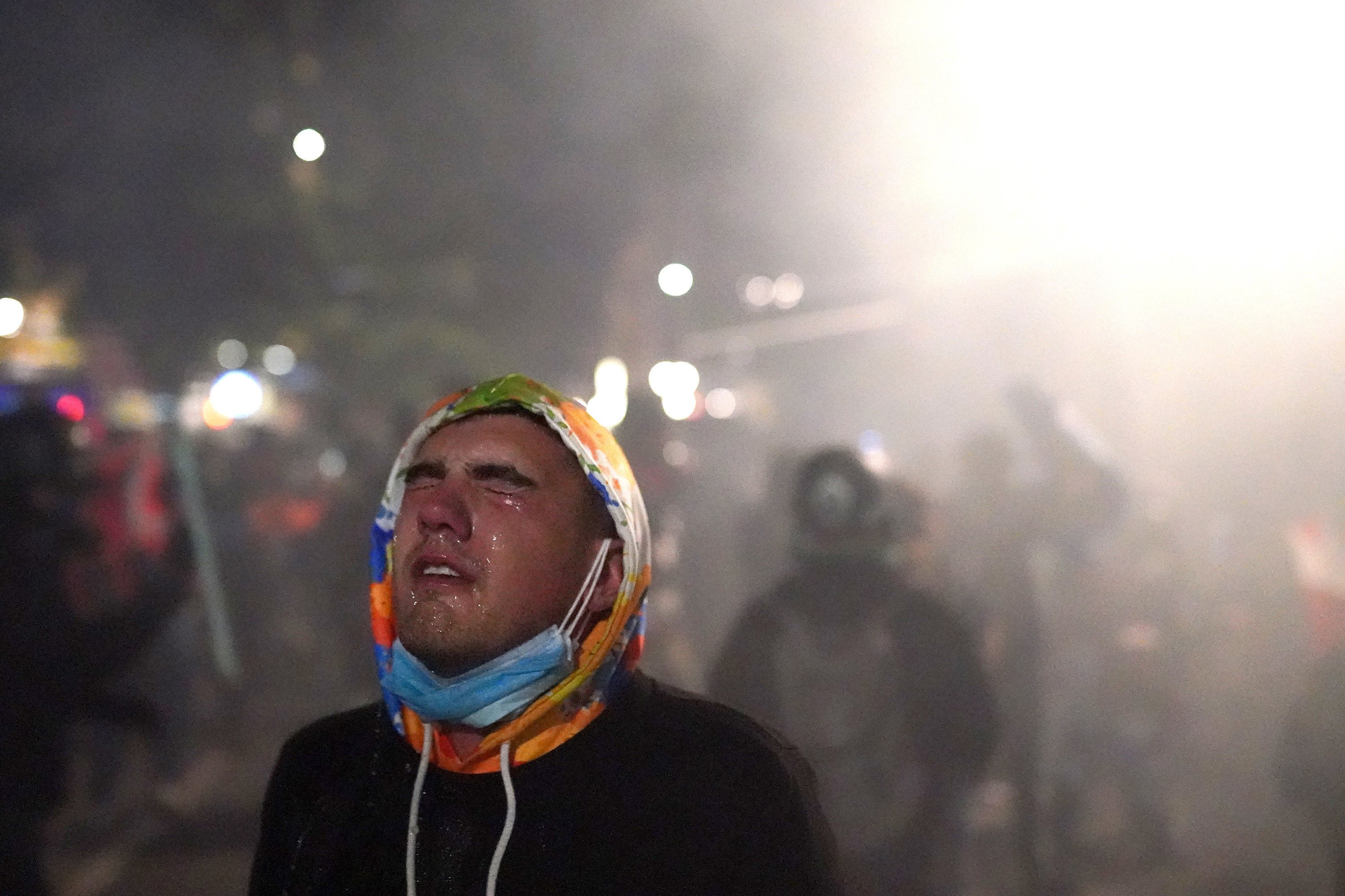 A protester closes his eyes as water steams from them after tear gas was fired by federal officers during a demonstration