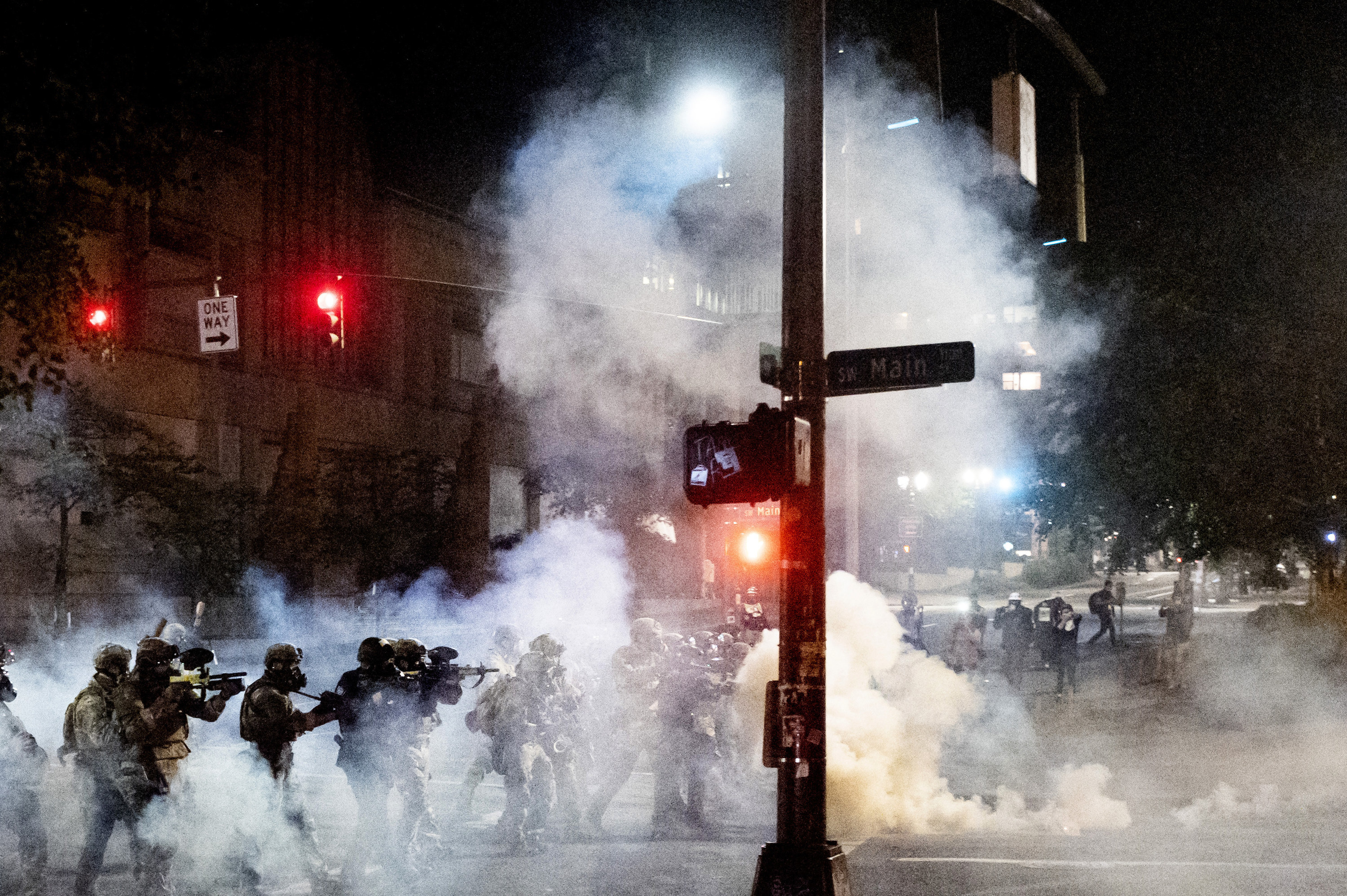 A group of federal agents walk through tear gas with crowd control munition devices that look like guns to disperse protesters